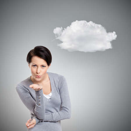 mystique: Beautiful lady throws a kiss, isolated on grey background with cloud