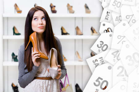 price uncertainty: Woman keeps two stylish pumps in the shopping mall and cant choose the one for her. Big sales season