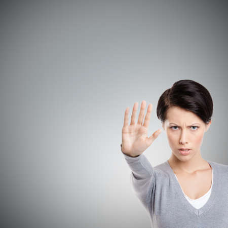 unkind: Smart girl shows stop gesture, isolated on grey background, close up Stock Photo