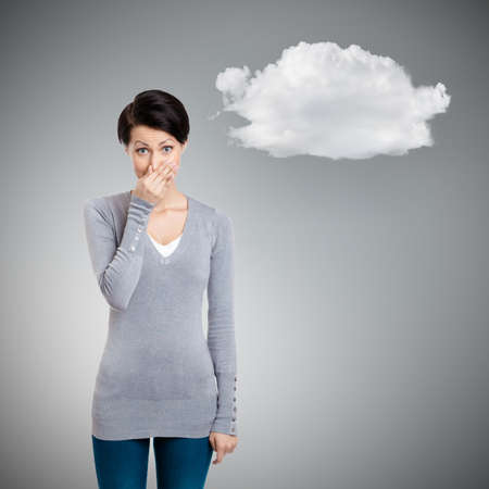 Young woman closes her nose with hand, isolated on grey background with cloud photo