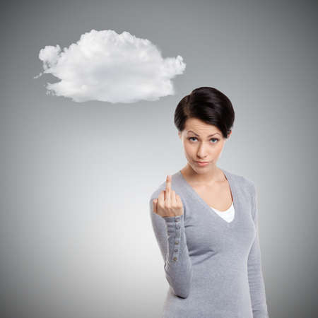 obscene: Attractive woman shows a vulgar, obscene finger sign, isolated on grey Stock Photo