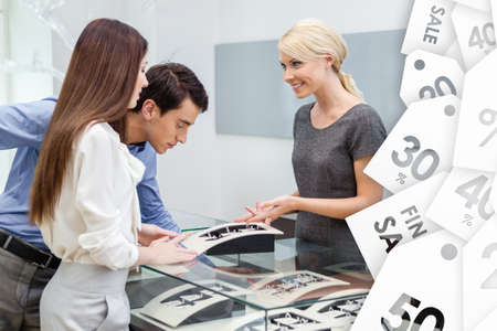 chose: Salesperson helps couple to select jewelry on sale at jewelers shop. Concept of wealth and luxurious life Stock Photo