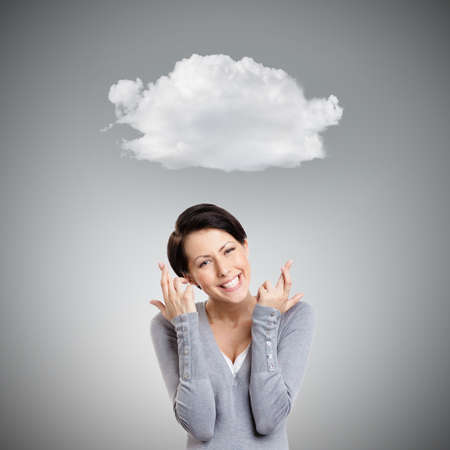 Young woman shows crossed fingers, isolated ongrey background with cloud photo