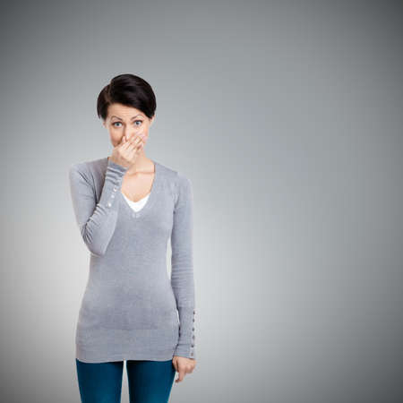 Young woman closes her nose with hand, isolated on grey photo