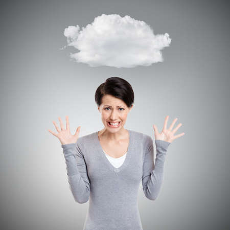 unkind: Desperate upset woman with cloud over her head, isolated on grey background Stock Photo