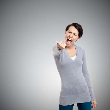 obscene: Attractive woman shows a vulgar, obscene finger gesture, isolated on grey Stock Photo