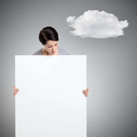 Woman brings a huge sheet of white cardboard, isolated on grey background with cloud photo