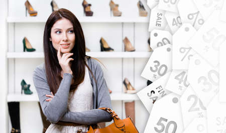 consumerism: Woman in shopping center in the section of female stylish shoes, clearance sale. Concept of consumerism and stylish purchase