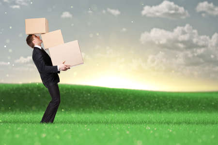Manager holding pile of pasteboard boxes, nature background photo