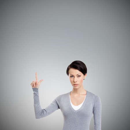 unkind: Young woman shows forefinger, attention sign, isolated on grey