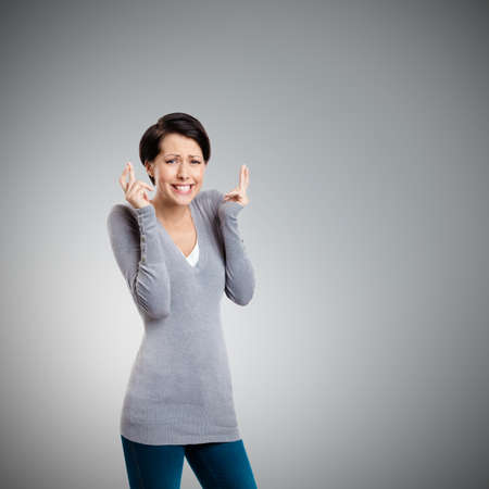 crossed fingers: Hoping young woman shows crossed fingers, isolated on grey Stock Photo