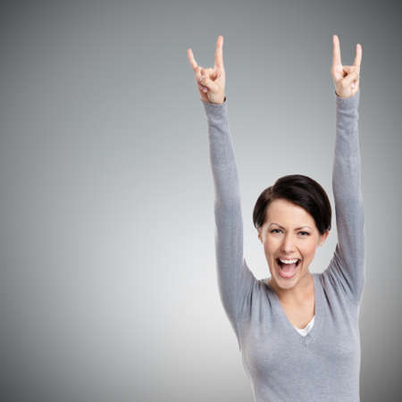 gust: Happy pretty woman puts her hands up, isolated on grey Stock Photo