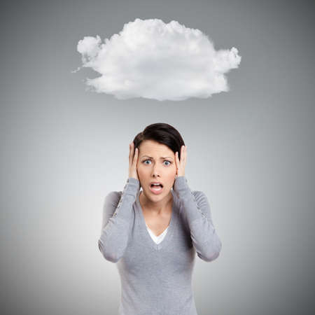 put pressure: Confused woman puts her hands on the head, isolated on grey background with cloud Stock Photo