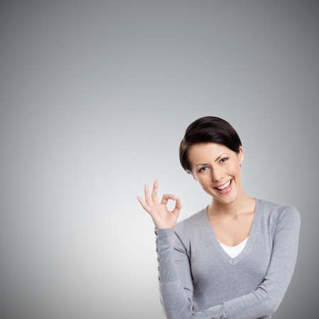lighthearted: Young lighthearted girl shows Okay gesture, isolated on grey background