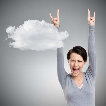 gust: Happy pretty woman puts her hands up, isolated on grey background with cloud Stock Photo
