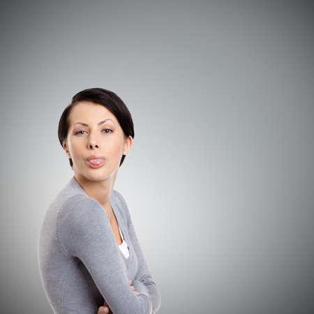 cansancio: Mujer bonita joven que se pega hacia fuera la lengua, aislado en gris
