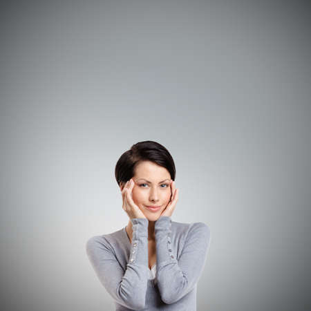 admires: Smart woman admires her own beauty, isolated on grey Stock Photo