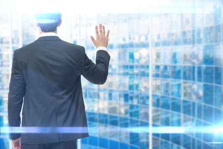backview: Backview of business man waving hand, blue background. Concept of leadership and success