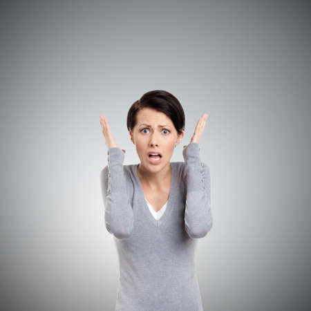 stress woman: Perplexed woman puts her hands on the head, isolated on grey
