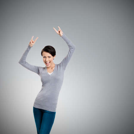 woman hands up: Glad pretty woman puts her hands up with two fingers pointed up, isolated on grey