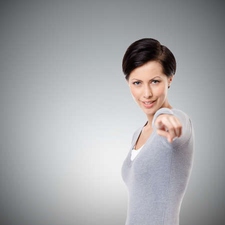 mystique: Playful girl shows imperious hand gesture, isolated on grey