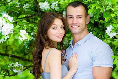 love tree: Beautiful couple embracing near blossomed tree in the park. Concept of love and stable relations Stock Photo