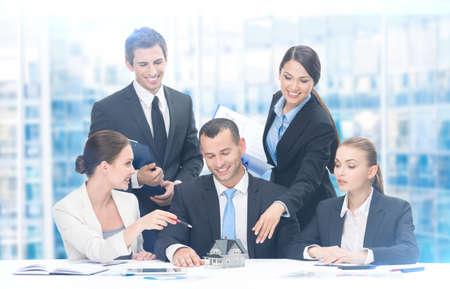 cooperacion: Grupo de ejecutivos que trabajan mientras está sentado en la mesa, fondo azul. Concepto de trabajo en equipo y la cooperación Foto de archivo
