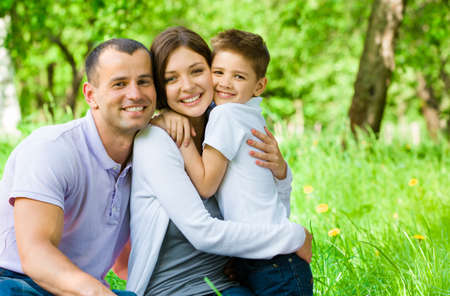 at leisure: Young family of three has picnic in park. Concept of happy family relations and carefree leisure time Stock Photo