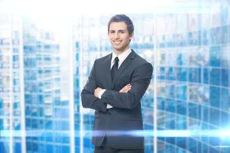 success man: Portrait of business man with crossed hands on blue background. Concept of leadership and success