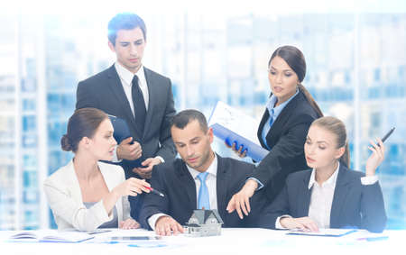 executive woman: Group of executives debating while sitting at the table, blue background. Concept of teamwork and cooperation
