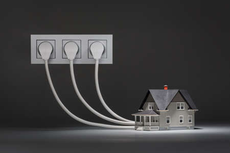 realty residence: Concept of increased consumption of electricity - small house on grey background