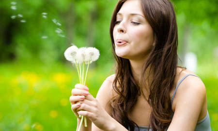 blow: Beautiful woman blows dandelions in the park. Concept of nature and rest