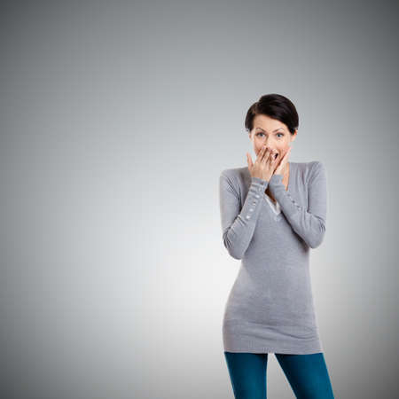 lighthearted: Woman covers her mouth with hand, isolated on grey