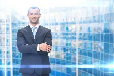 success man: Portrait of business man with hands crossed on blue background. Concept of leadership and success Stock Photo