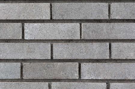 Grey brick wall background closeup