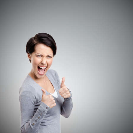 Emotional pretty girl gives thumb up, isolated on grey Standard-Bild