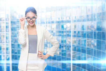Portrait of businesswoman wearing glasses, blue background. Concept of leadership and success Standard-Bild