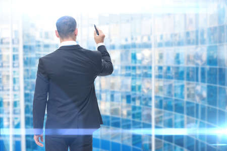 backview: Backview of businessman writing with marker on imaginary screen, blue background. Concept of leadership and success Stock Photo
