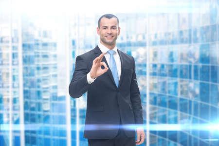 Portrait of businessman ok gesturing, modern background. Concept of leadership and success Standard-Bild