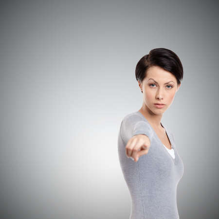 Serious decisive girl points hand gesture, isolated on grey Stock Photo