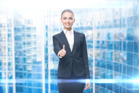 Portrait of business woman who thumbs up, blue background. Concept of leadership and success Standard-Bild