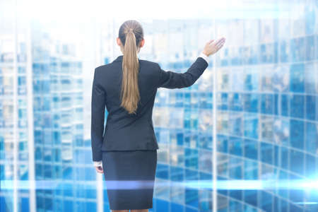 backview: Backview of young business woman waving her hand, blue background. Concept of leadership and success