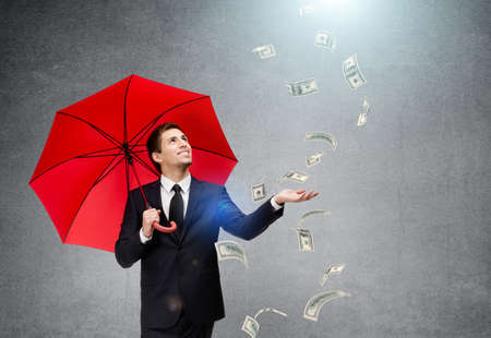 Palming up man with opened umbrella looking at falling money, isolated on white. Concept of profit and successful business