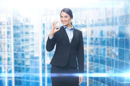 Portrait of businesswoman ok gesturing, blue background. Concept of leadership and success Standard-Bild