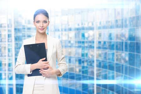 Portrait of businesswoman handing black folder, blue background. Concept of leadership and success Standard-Bild