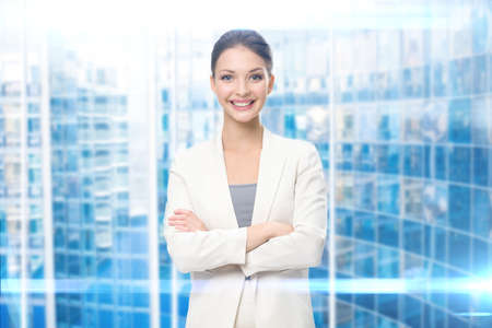 Half-length portrait of business woman with arms crossed, blue background. Concept of leadership and success