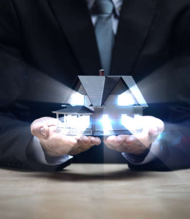 Close up of hands with little home shining. Concept of deal and real estate