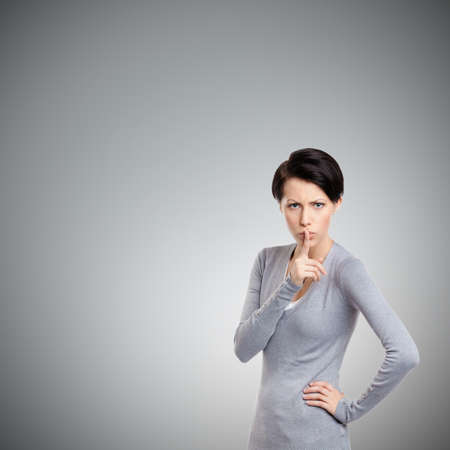 unkind: Pretty woman shows shush gesture, isolated on grey background