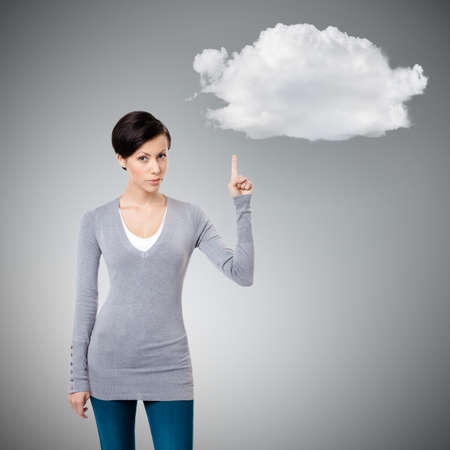 Young girl shows forefinger, attention sign, isolated on grey background with cloud