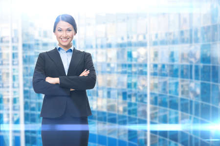 formats: Portrait of businesswoman with hands crossed, blue background. Concept of leadership and success Stock Photo